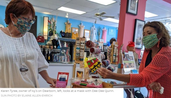 Kaen Tyree, owner of Ivy's on Dearborn, left, looks at a mask with Dee Dee Quinn.  Sun Photo by Elaine Allen-Emrich